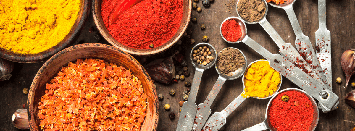 variety of coloured spices in jars and measuring spoons