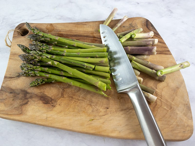 ASPARAGUS ON A WOODEN BOARD THAT HAS BEEN CUT