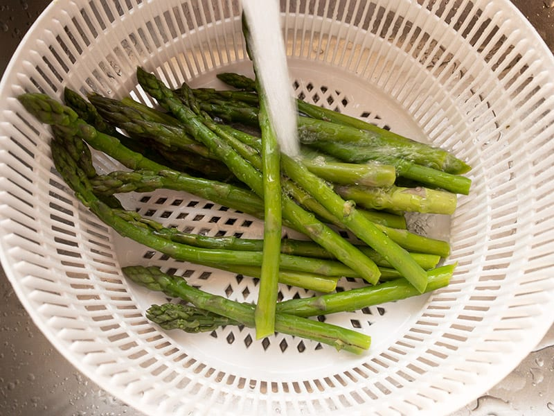 REFRESHING BLANCHED ASPARAGUS UNDER COLD RUNNING WATER IN COLANDER IN A SINK