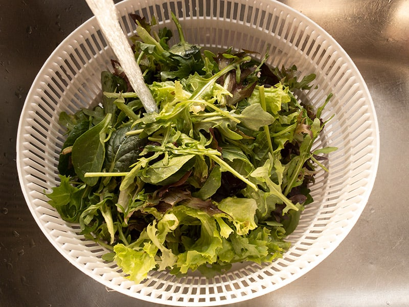 WASHING SALAD LEAVES IN STRAINER UNDER COLD WATER