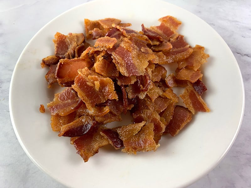 CRUMBLED COOLED BACON ON A WHITE PLATE