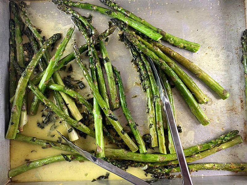 06-TOSSING-ROASTED-ASPARAGUS-WITH-OIL,-HERBS-AND-VINAIGRETE