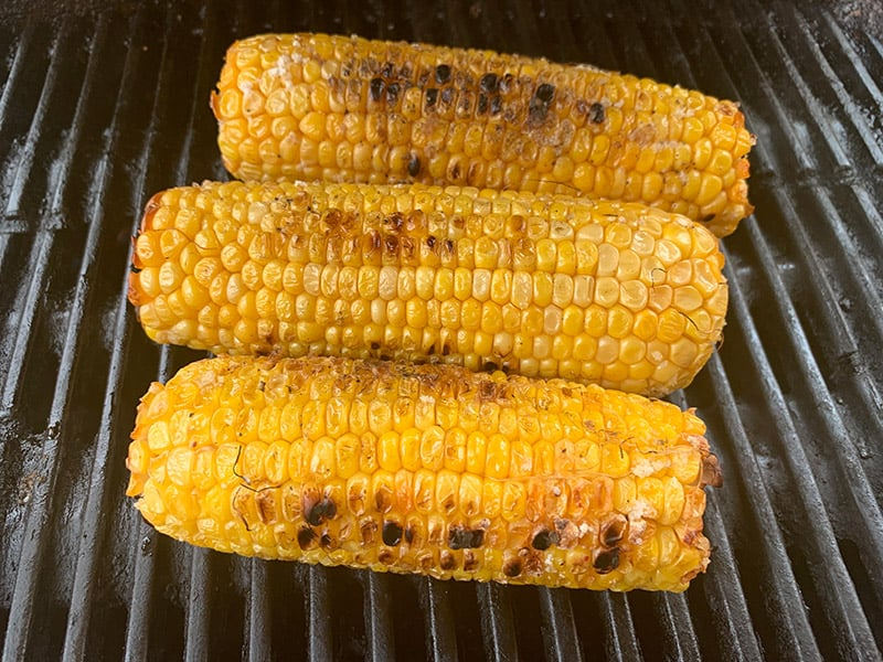 GRILLING CORN ON BBQ UNTIL CHARRED & SOFT