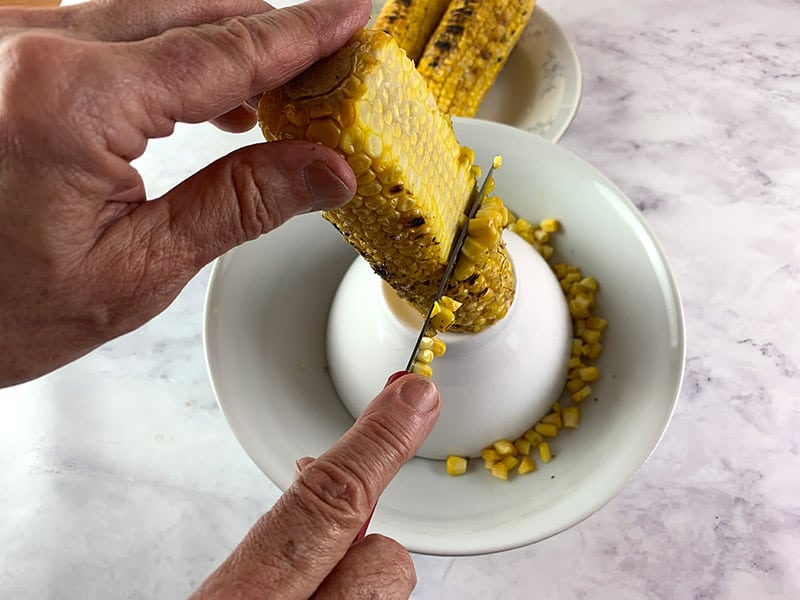STANDING CORN COB IN BOWL AND CUTTING OFF KERNELS