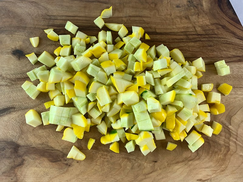 DICING PATTYPAN SQUASH ON WOODEN BOARD