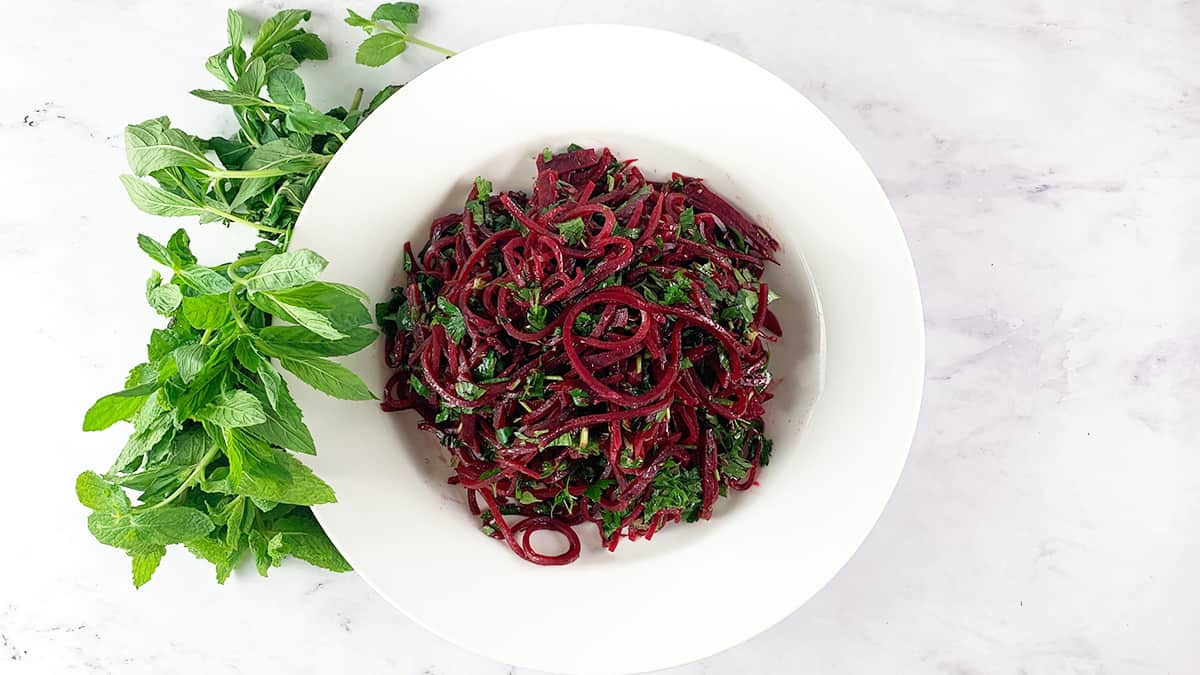 beetroot spirals in white bowl with mint