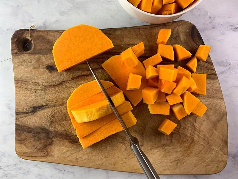 Knife dicing pumpkin on wooden board