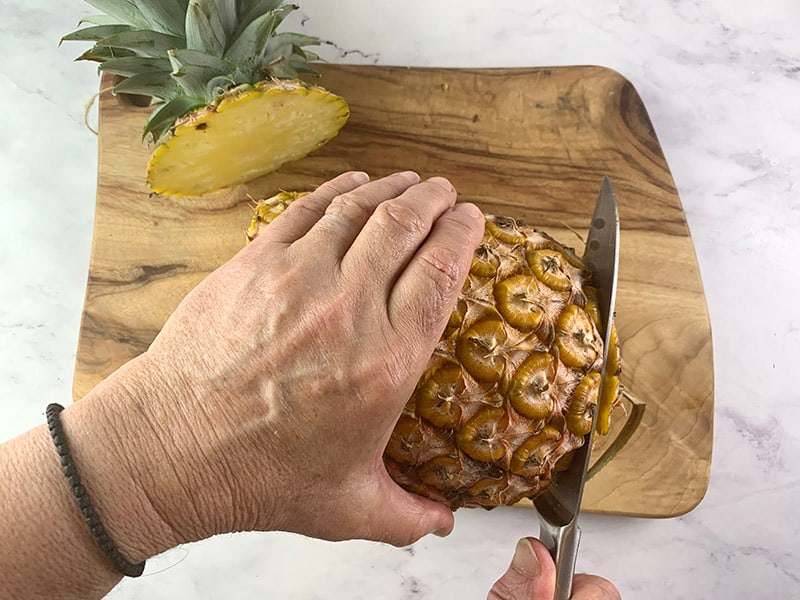 CUTTING THE BOTTOM FROM A PINEAPPLE