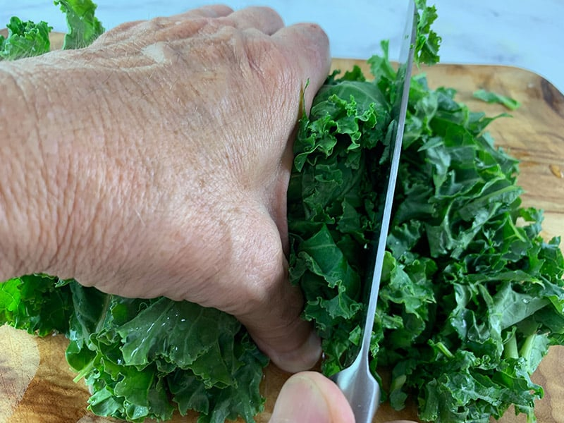 Cutting kale with knife on a chopping board