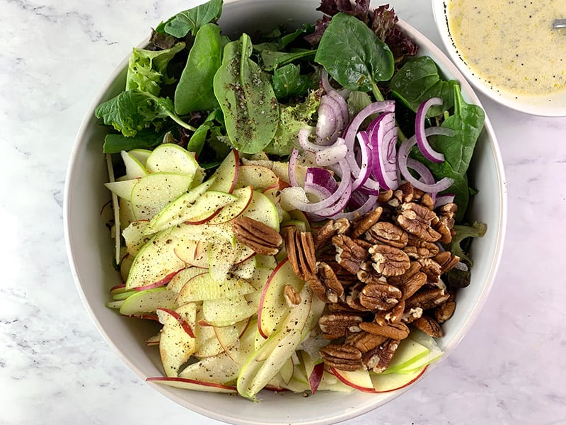 ALL THE INGREDIENTS FOR APPLE PECAN SALAD IN A MIXING BOWL WITH DRESSING ON THE SIDE