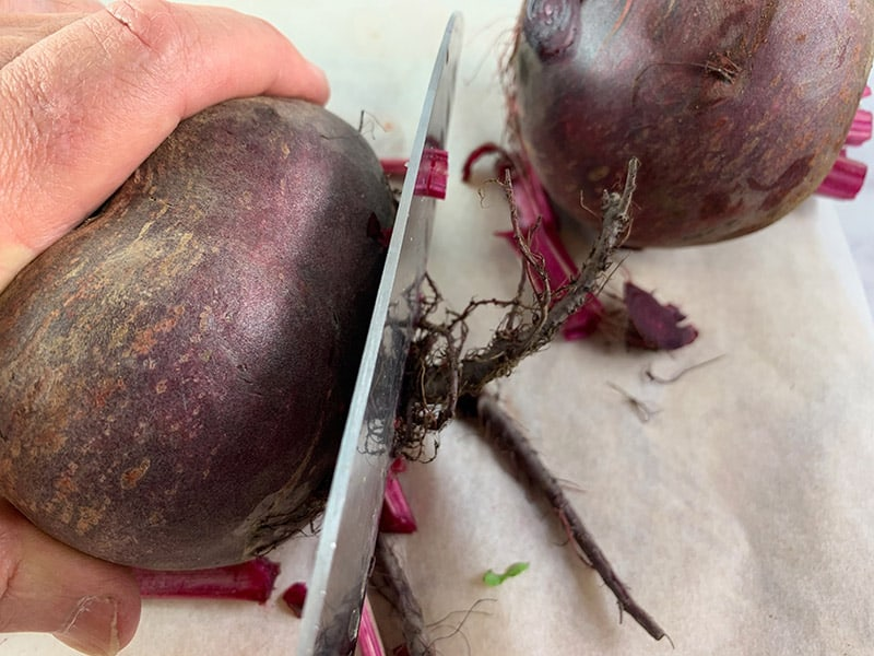 CLOSE UP OF TRIMMING BEET ROOTS