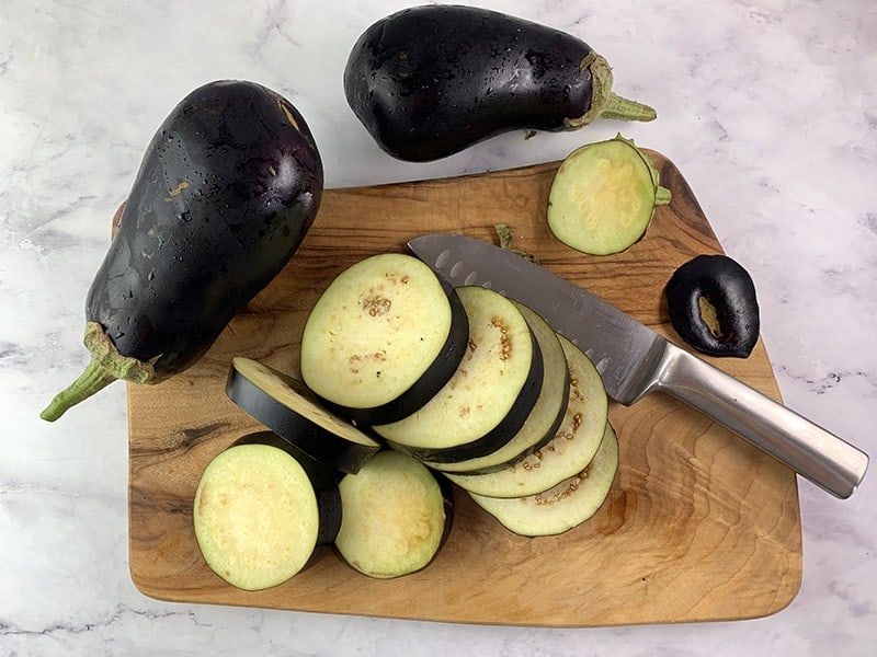 CUTTING EGGPLANTS INTO ROUNDS WITH A KNIFE ON A WOODEN BOARD