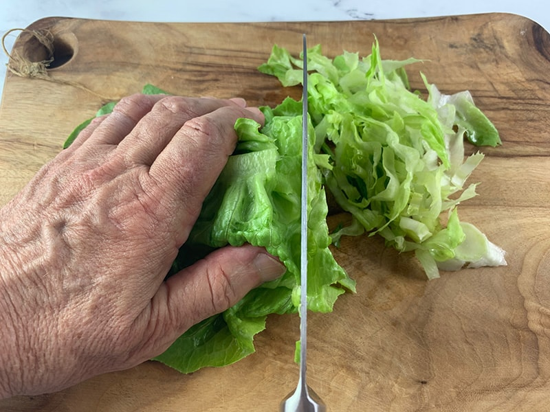 SHREDDING LETTUCE WITH A KNIFE ON A WOODEN BOARD