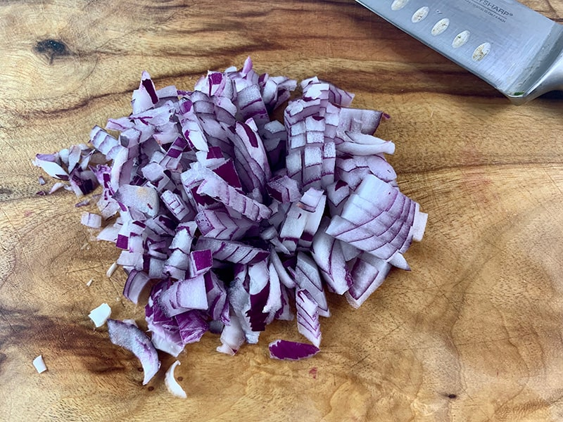 DICING RED ONION INTO A SMALL DICE ON A WOODEN BOARD
