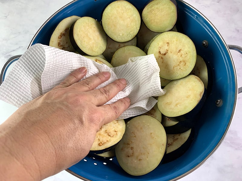 PATTING EGGPLANT ROUNDS IN A COLANDER TO REMOVE WATER BEADS