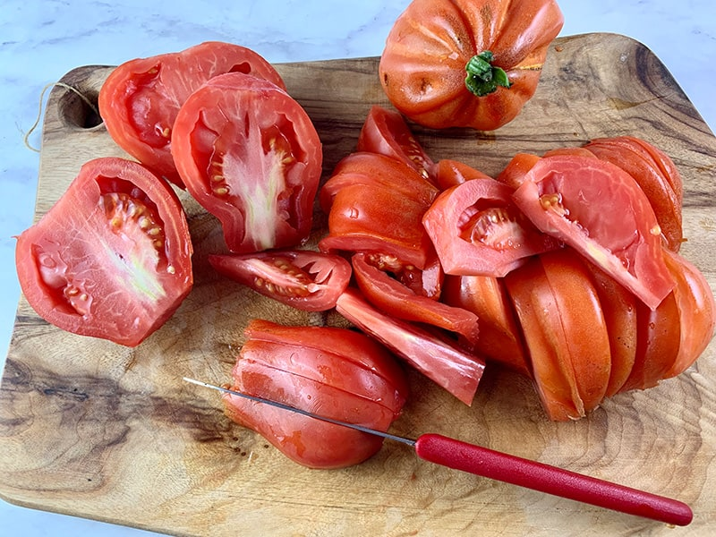CUTTING HEIRLOOM TOMATOES INTO WEDGES ON A WOODEN BOARD WITH A SMALL RED SERRATED EDGE KNIFE