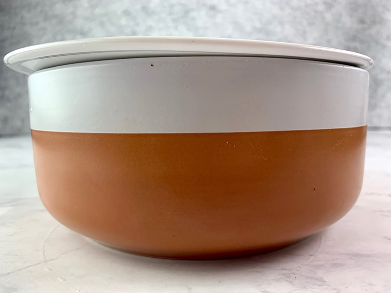 A TERRACOTTA & WHITE BOWL WITH A PLATE ON TOP
