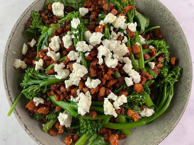 SCATTERING CRUMBLED FETT ON TOP OF BROCCOLINI SALAD WITH CHORIZO