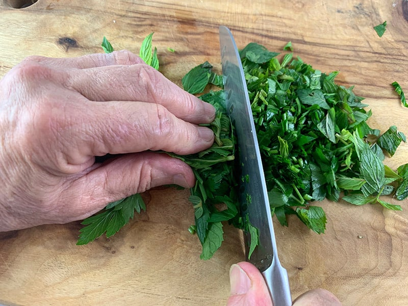 ROUGHLY CHOPPING MINT & PARSLEY ON A WOODEN BOARD WITH A KNIFE