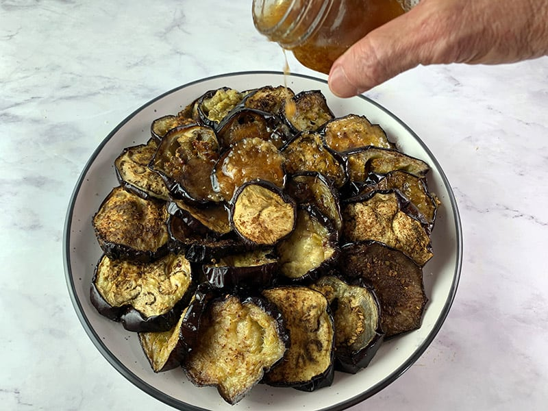 POURING VINAIGRETTE OVER ROASTED EGGPLANT ROUNDS