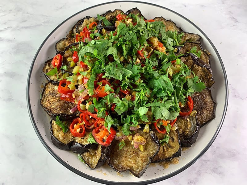 ADDING CHOPPED CORIANDER (CILANTRO) TO ROASTED EGGPLANT ROUNDS WITH CHILLI MIX