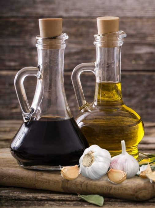 SWEET BALSAMIC INGREDIENTS, OLIVE OIL AND BALSAMIC VINEGAR IN GLASS BOTTLES WITH GARLIC ON A WOODEN BOARD