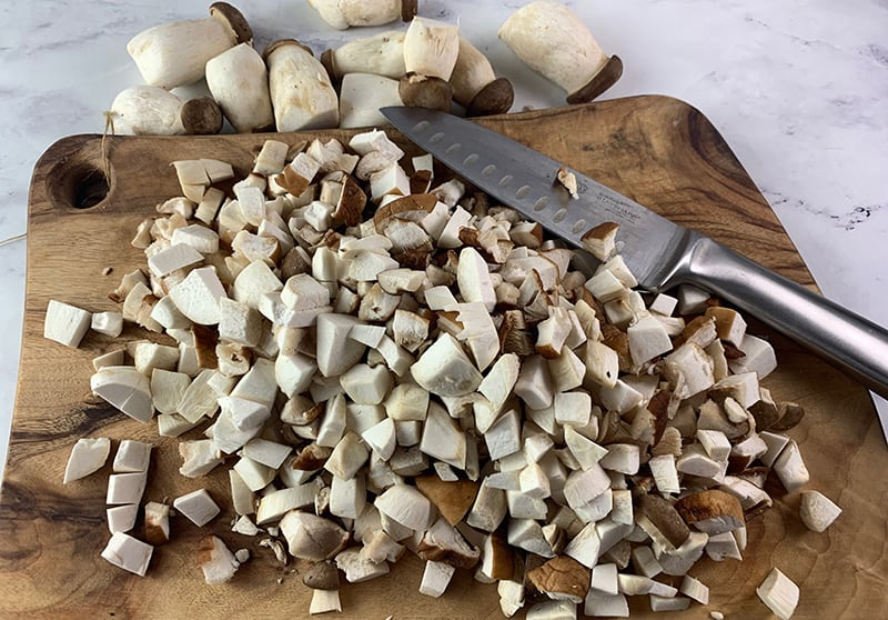 DICING MUSHROOMS ON WOODEN BOARD
