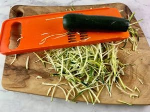 CUTTING LONG DARK GREEN ZUCCHINI INTO JULIENNE STRIPS WITH V-SLICER
