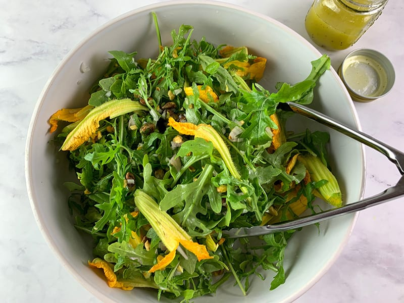 MIXING ARUGULA SALAD INGREDIENTS IN A WHITE BOWL