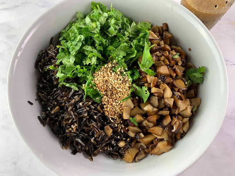 ADDING ALL WILD RICE SALAD INGREDIENTS TO A WHITE BOWL