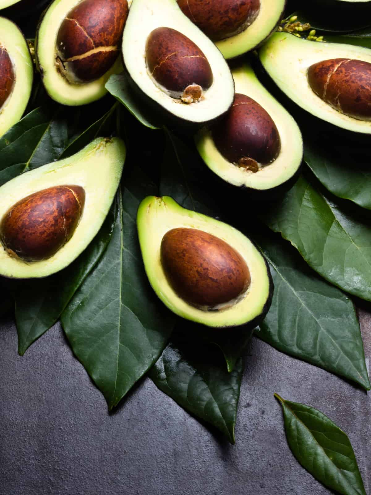 CUT AVOCADOS ON DARK GREY BACKGROUND