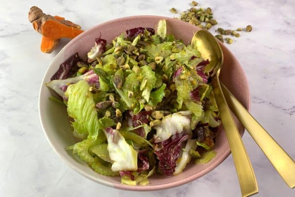 MIXED GREEN SALAD WITH TURMERIC DRESSING IN A PINK BOWL WITH GOLD CUTLERY ON WHITE MARBLE BACKGROUND