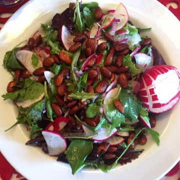 SPRING RADISH SALAD WITH ALMONDS AND ARUGULA IN AERIAL VIEW
