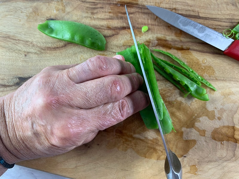CLOSE UP OF SLICING SNOW SNAP PEAS JULIENNE STYLE