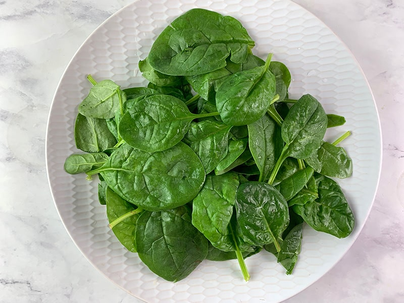 WASHED BABY SPINACH ON A WHITE PLATE