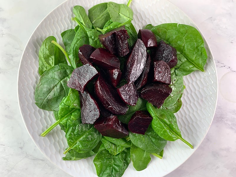 WASHED BABY SPINACH, RED BEETS ON WHITE PLATE