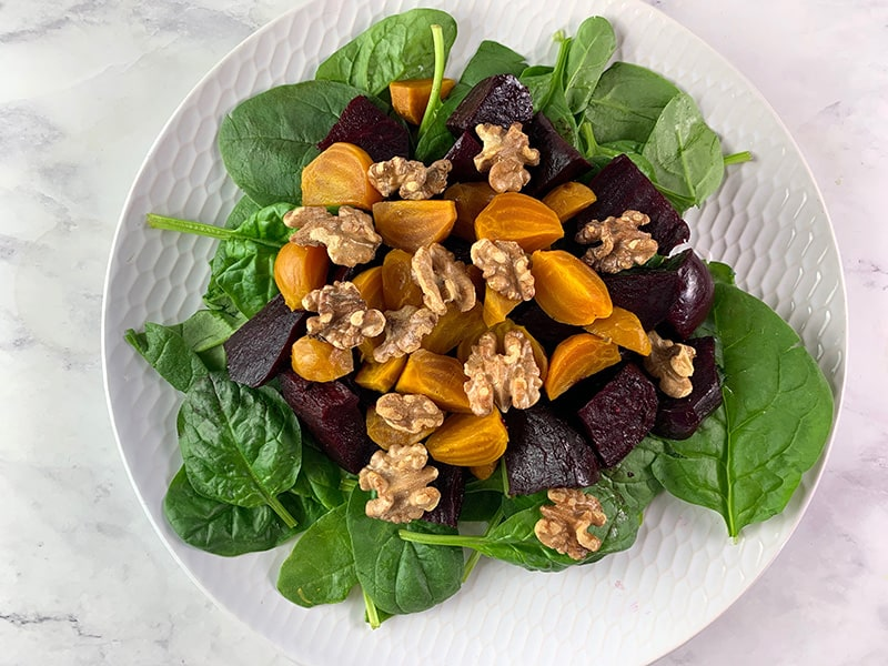 WASHED BABY SPINACH, RED BEETS, GOLDEN BEETS & WALNUTS ON WHITE PLATE