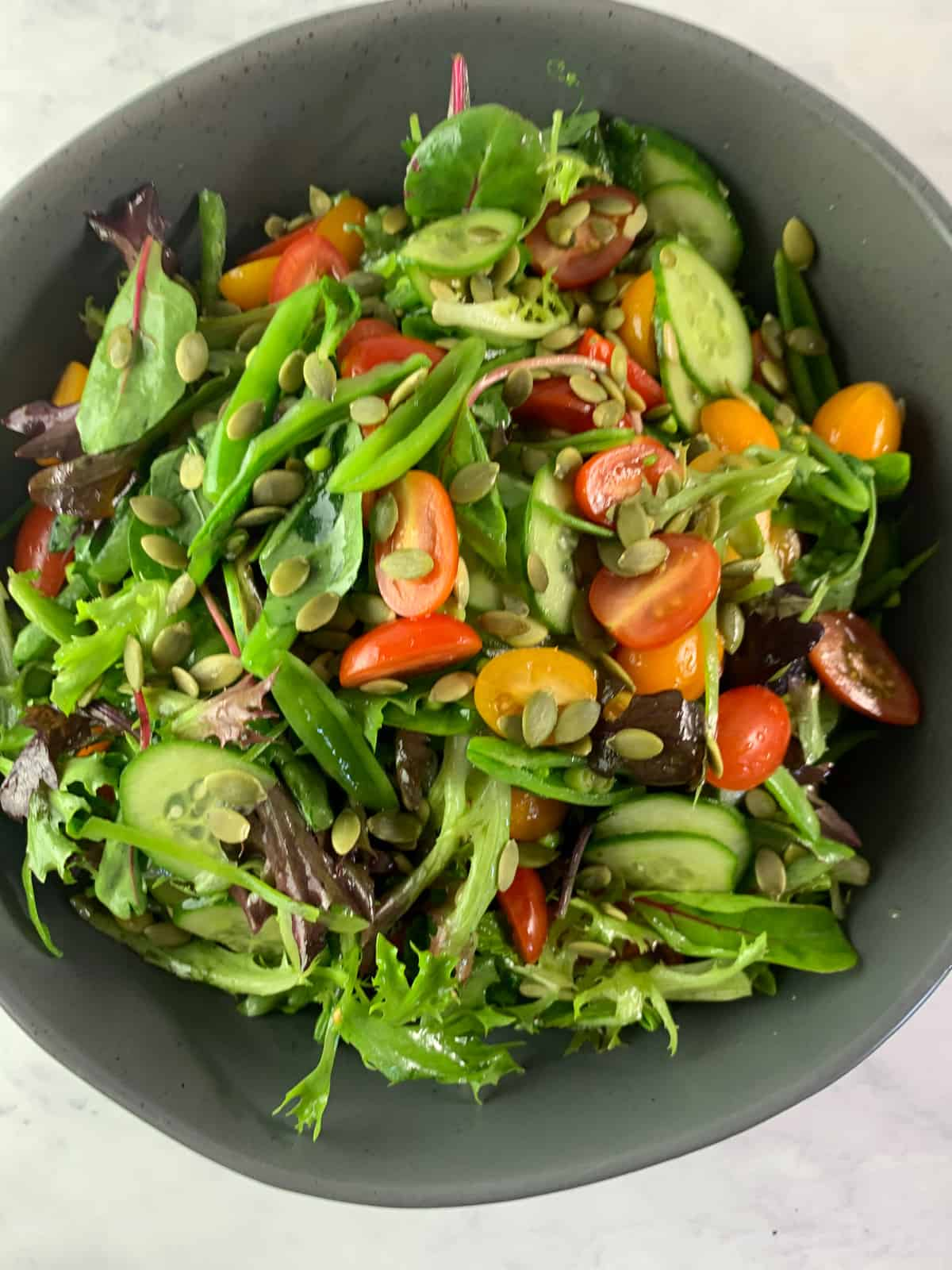 CLOSE UP OF SPRING MIX SALAD WITH PEAS, TOMATOES, CUCUMBERS AND SEEDS