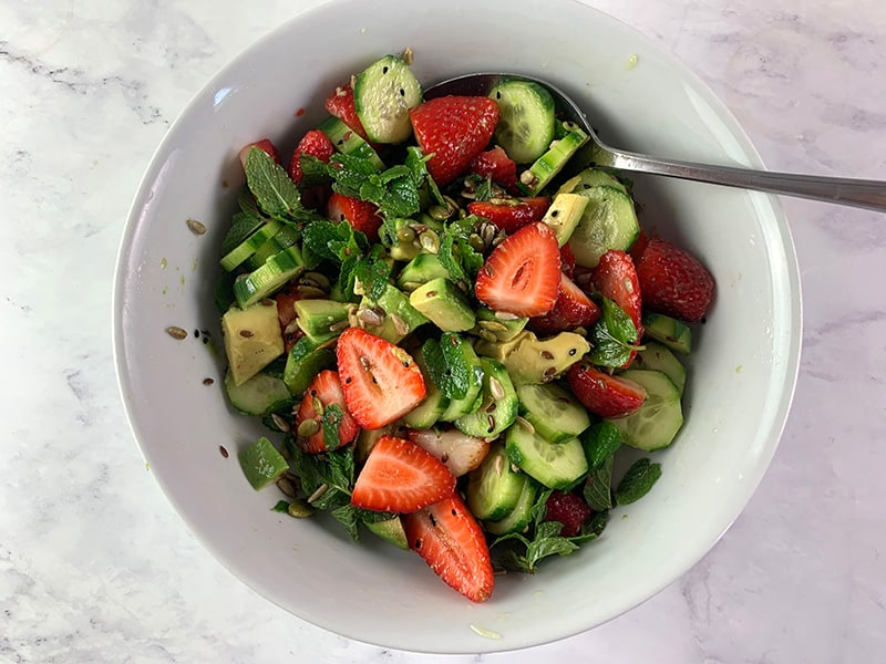 MIXING CUCUMBER STRAWBERRY SALAD IN BOWL