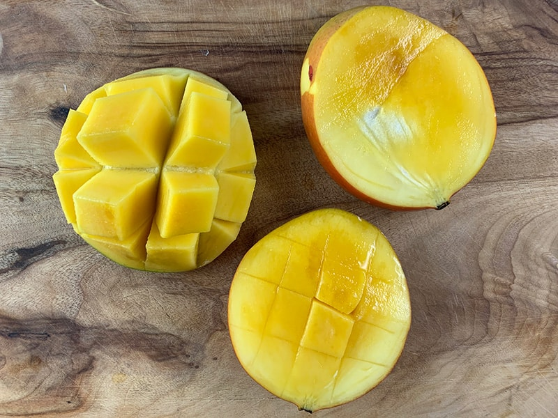 CUTTING A MANGO ON WOODEN BOARD