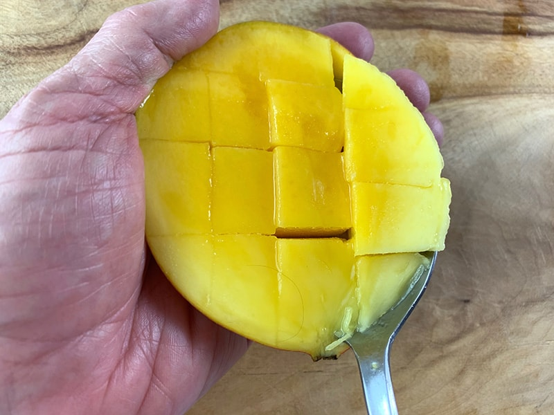 SCOOPING MANGO FLESH WITH A SPOON ON A WOODEN BOARD