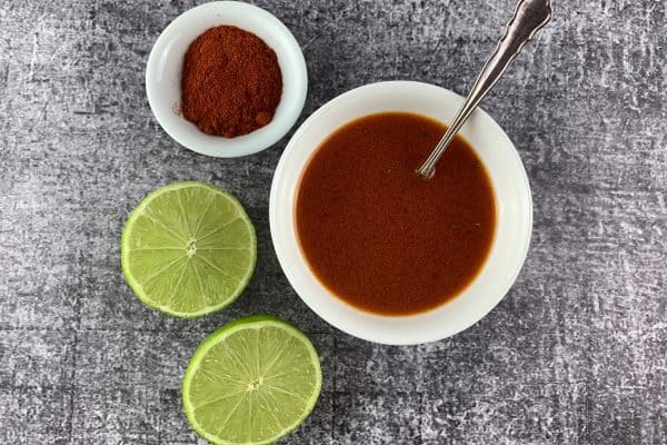 SMOKED PAPRIKA VINAIGRETTE IN WHITE BOWL WITH LIMES AND PAPRIKA LANDSCAPE VIEW