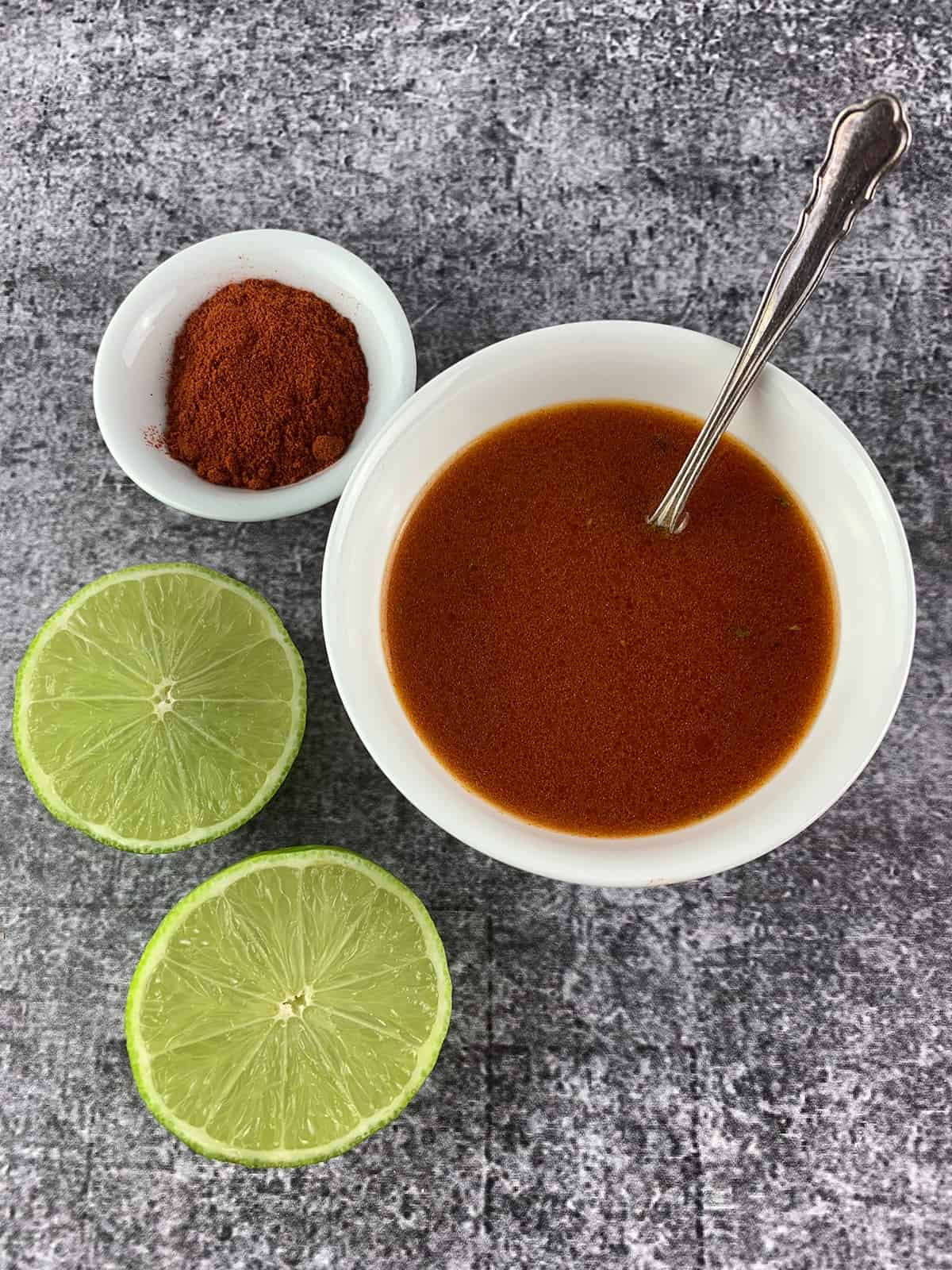 SMOKED PAPRIKA VINAIGRETTE IN WHITE BOWL WITH LIMES AND PAPRIKA PORTRAIT VIEW