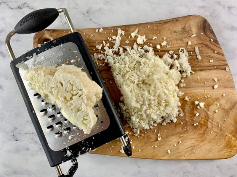 GRATING CAULIFLOWER WITH BOX GRATER ON WOODEN BOARD