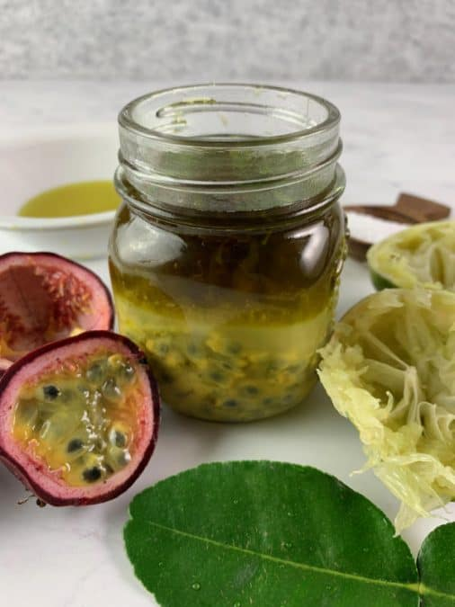 INFREDIENTS FOR PASSION FRUIT DRESSING IN GLASS JAR WITH CUT PASSIONFRUIT, LIMES & LIME LEAVES