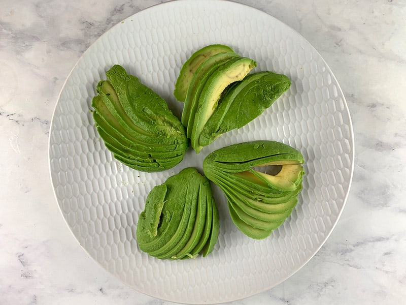 Avocado halves fanned on a white plate