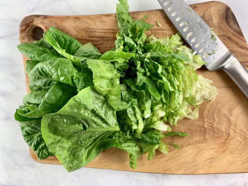 SHREDDING WASHED LETTUCE ON A WOODEN CHOPPING BOARD WITH A KNIFE