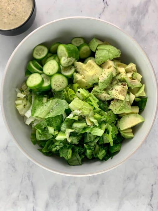 ROMAINE AVOCADO SALAD INGREDIENTS IN BOWL WITH DRESSING ON THE SIDE