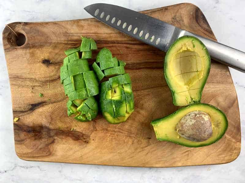 DICING SHEPHARD AVOCADOS ON WOODEN BOARD