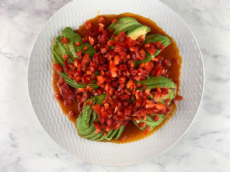 DICED RED PEPPER ON FANNED AVOCADO WITH DRESSING